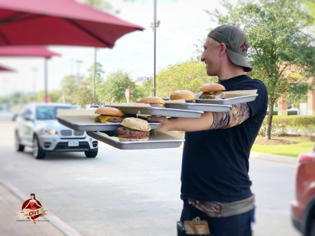 server with 5 burgers on his arm at HopDoddy Burger Bar
